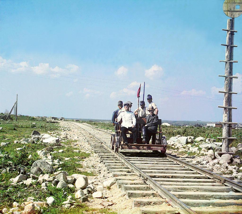 Gente yendo en dresina — un carro para ir en ferrocaril que mueve a mano. Fueron muy usados en el siglo XIX especialmente para las tareas de arreglo de ferrocarriles.